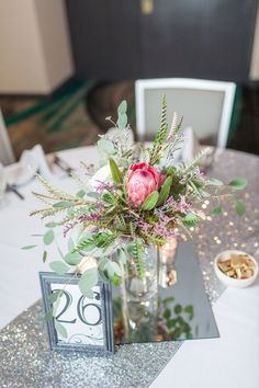 Loved it! Pinned it! A Blooming Envy Design! Photo by Ashlea Snell Photography. Centerpiece designed with Pink Ice Protea, Blush Garden Roses, Eucalyptus and Grevillea.