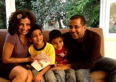 The prolific author strikes a pose with wife Anusha and kids.