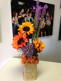 Harvest Gold! Purple liatris and allium accent the powerful orange tinted sunflowers and cute daisy pomps; everything works together in harmony to create an adorable conversation piece.