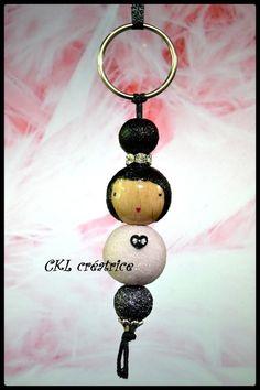 Porte-clés poupée perles bois.  Peut aussi être utilisé en bijoux de sac à main.  Les perles en bois sont peintes et vernies à la main.  Perles tête noires pailletées (12 et 18mm), perle corps blanche pailleté (18mm), perle du bas grise pailletée (12mm) et calottes argentées.  Hauteur poupée 6 cm, hauteur total avec attache 10 cm.  Fait main.  Elle est livrée dans une jolie petite boîte.