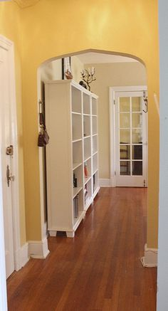 I like the archway, the yellow paint color, the bookcase, and the french doors in the background