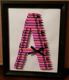 Crayon letter out of pinks & purples only.
