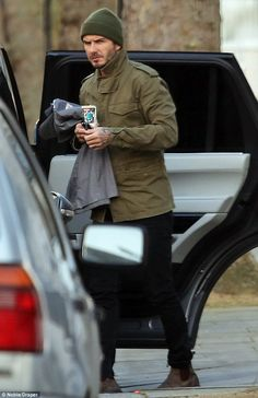 Holding the fort: David Beckham carries his daughter Harper's belongings as he heads home ...