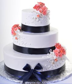 Pastry Palace Las Vegas - Wedding Cake #930 – Just Enough. White whipped cream frosting with black ribbon, white and coral scrolls and flowers.