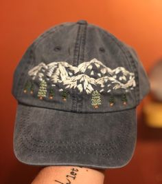 This is a hand embroidered design by yours truly! The hat is an Adams brand hat and is in a nice midnight blue color. It features a leather strap in the back for sizing purposes. Fun fact: the inspiration behind this hat is the very talented Bob Ross. Silk Ribbon Embroidery, Embroidery Art, Cross Stitch Embroidery, Embroidery Patterns, Modern Embroidery, Embroidered Baseball Caps, Embroidered Hats, Bone Bordado, Happy Little Trees