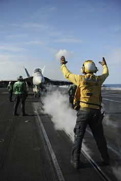 "PACIFIC OCEAN (Dec. 2, 2013) Aviation Boatswain's Mate (Handling) 3rd Class Joseph Farrellbrew directs an F/A-18E Super Hornet, assigned to the ""Argonauts"" of Strike Fighter Squadron (VFA) 147, prior to launching on the flight deck of the aircraft carrier USS Nimitz (CVN 68). (U.S. Navy photo by Mass Communication Specialist 3rd Class Siobhana R. McEwen/ Released)"
