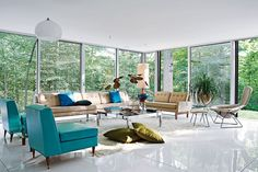 The living room of the Goddard-Mandolene residence in Westchester County, originally designed by architect Arthur Witthoefft in 1957, features vintage furnishings by Harry Bertoia, Paul McCobb, and others, and overlooks its heavily wooded site. Goddard and Mandolene replaced the original tile floor with a glossy coat of resin and restored the original ceiling.    This originally appeared in Blues Clues .