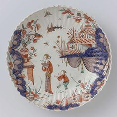 De Grieksche A | Schaal van veelkleurig beschilderde faïence, De Grieksche A, Pieter Adriaensz. Kocx, c. 1700 - c. 1725 | Ronde schaal van veelkleurig beschilderde faïence, met een geribde rand. De schaal is beschilderd met een Japans (?) decor. In een landschap staan twee figuren. Links is een tafel waarop een vaas met bloemen geschilderd en rechts een huis, waaronder een baldakijn. De schaal is gemerkt en hoort bij een identieke schaal.