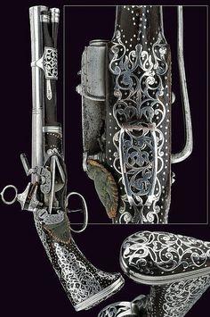 """Pistola Catalana d'inicis del segle XVIII amb pany Miquelet, penja-xarpa, empunyadura de """"cua de peix"""", totalment decorada amb el que sembla argent. Te moltes possibilitats de ser una manufactura de Ripoll."""