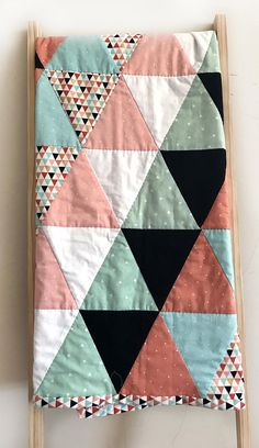 In stock and ready to ship. This modern baby quilt is carefully handcrafted with 100% cotton. It features bright and vibrant pinks and blues on top with a black and white polka dotted back. It is perfect for a crib or to use for tummy time. This quilt is the perfect addition to your