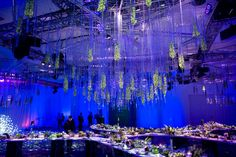 Suspended glass vessels accented with fresh flowers hovered over the dinner and award space.