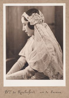 House of Worth, 1933 Photograph mounted on cream card of the Baronne de Rochefort-Sirieyx in a satin wedding dress. The dress has a V-neckline and smocking at the shoulders and leg-of-mutton sleeves. She wears a plaited headdress with a veil of late 19th/early 20th century mixed Brussels Duchesse lace. Fashion Museum Bath