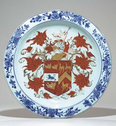 AN ARMORIAL CHARGER  Circa 1720  Boldly painted in the center with a large coat-of-arms of Gough impaling Hynde against exuberantly scrolling acanthus leaves and beneath the boar's head crest, the rim with clusters of flowering branches in bright tones of underglaze blue.
