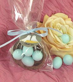 """Offer your guests the cutest little gift of appreciation with our Love Nest Soap favors!  Wrapped in a crisp cello bag, and accented with matching blue satin ribbon, you'll find a 2-inch diameter straw bird's nest.  Within the nest are four 1.2-inch long soaps in a delightful egg shape, and featuring a recognizable robin's egg blue color.  A matching Love Birds-themed favor tag reading """"Thank You"""" completes the presentation.  The honored """"Love Birds"""" at your shower or event will enjoy seeing…"""