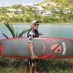 Jimmy Buffett poses with the surfboard from Apocalypse Now.
