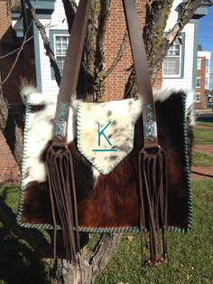 A custom made to order Buckaroo Tote with turquoise suede lace and brand. Lined with two interior pockets. Hand cut suede fringe and decorative silver conchos with a small turquoise stone accent the straps. Order your custom bag at gowestdesigns.us
