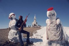 AIM activist with rifle stands guard in front of Sacred Heart Church with two freshly built snowmen after a blizzard at Wounded Knee. The church was later burned down, 1973  Photo credit: Jim Hubbard