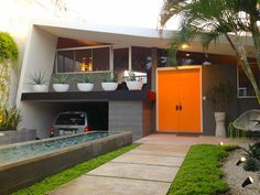 I like the green plants and the garage and the grey color with the orange door which give it a nice touch