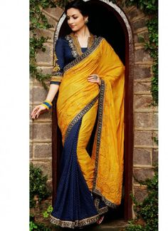 """Elegant Yellow & Blue Silk & Jacquard Saree. Silk and banarsi jacquard lehenga saree adorned with stone,resham and patch border work, teamed up with designer blouse. As shown the blouse can be made available and also can be customized upto 42"""" available at just Rs. 8350/-"""