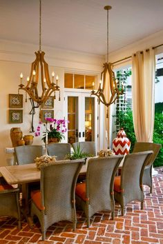Fabrics, artwork and lighting turn this outdoor living space into another room of the house. The dining table for eight rests on a brick terrace, and dual chandeliers add warmth and ambiance. Accessories add elegant, rustic charm.