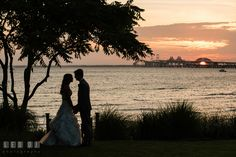 Silhouette of Bride and Groom holding hands with beautiful sunset view of the Chesapeake Bay and the Bay Bridge. Kent Island Maryland Chesapeake Bay Beach Club wedding photo, by wedding photographers of Leo Dj Photography. http://leodjphoto.com