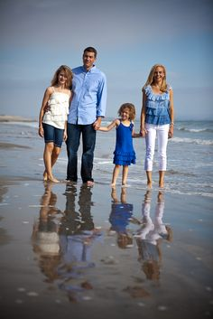 Like the different twist on the traditional family beach photograph with white and khaki AND the relections captured in the water.