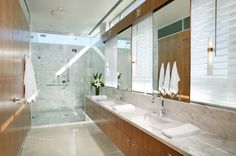 Sparkling mixture of bright marble and natural wood tones throughout this lengthy bathroom. Dual vanity with marble backsplash over floating cabinetry places mirrors between lengths of window, while all glass shower takes up end of the room.
