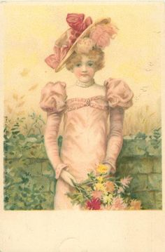 woman in pink dress & ornate hat stands, holding flowers, in front of low green wall