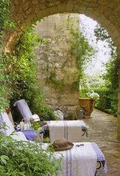 An Italian garden room with lavender blue accented loungers.