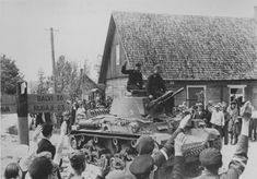Latvian town residents welcome tank Pz.35 (t) of the 6th Armored Division of the Wehrmacht.