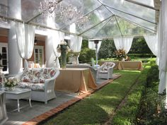 Clear tent with with pole wrap, leg drapes, and clear Maria Theresa chandeliers.