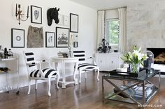 Black and white living room // I love the pom pom edging on the curtains, the striped upholstery on the chairs and the mix of 3d and 2d salon style wall art