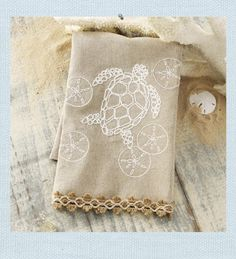 Sea Turtle Towel. Burlap and croched trim provides a textural element to our linen hand towel. Embroidered sea turtle design with sand dollar accents for the kitchen or bath.