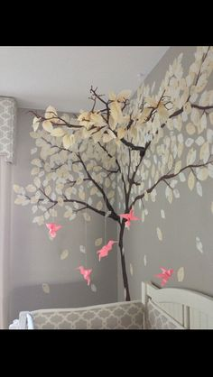 DIY nursery mobile with artificial manzanita branch, origami leaves, and origami hummingbirds