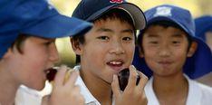 school boy eating a plum