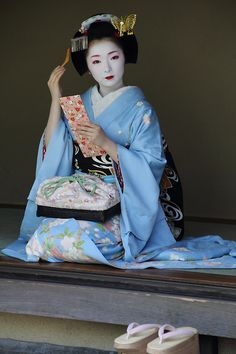 Maiko in blue. the red color around the eyes and eyebrows is also youthful. As the women get older the red starts lessen and eventually be left out completely.