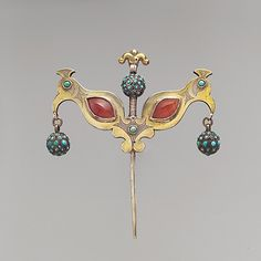 Central Asia or Iran   Headdress Ornament in the shape of a double bird   Late 19th to early 20th century   Silver, fire-gilded, with chip-carved decoration, cabochon carnelians, turquoise-beaded balls, and links