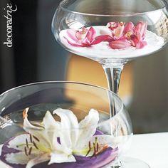Jarrones de cristal con flores en lecho de arena