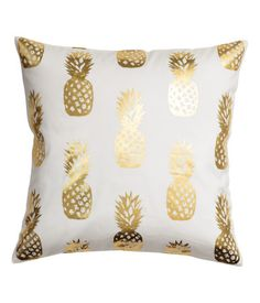 Vit. Ett kuddfodral i bomullstwill med tryckt, skimrande ananasmönster. Dold dragkedja.