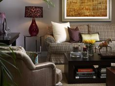 The high style of this living room recalls Hollywood in its heyday. Deep, soft upholstery contrasts the clean lines of the coffee table and art deco desk. While mostly neutral grays and beiges were used throughout, the purple Murano glass lamp and the eggplant-colored pillow add a bit of color.
