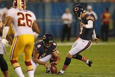 Robbie Gould #9 of the Chicago Bears kicks a field goal out of the hold of Adam Podlesh #8 against the Washington Redskins during a preseason game at Soldier Field on August 18, 2012 in Chicago, Illinois
