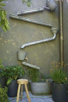 Love this water feature - made out of all zinc products -  guttering, watering cans, old funnel and bucket with a tap attached... so clever