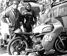 Anke Eve Goldmann mixing with other motorcyclists and examining a Norton Manx at Nurburgring -1956