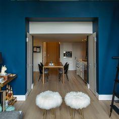 """<p style=""""text-align: justify;"""">Entre le salon et la petite cuisine-salle à manger, l'architecte a conçu des placards """"nichés"""" dans les cloisons. Table en bois l..."""