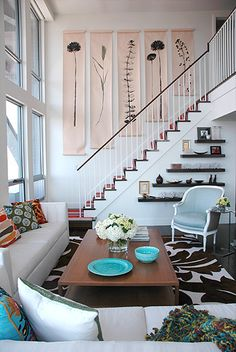 Interior Design: Spazio Rosso  Like scroll wall hangings; staggered shelves on stairs; rug!
