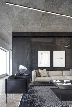 Axelrod renovates a Bauhaus-style loft in Tel Aviv | A free-standing container with a black steel patina finish that floats in the middle of the open plan space solved the practicalities of the design. It hides an en suite bathroom, guest bathroom and powder room, storage and a laundry room. Meanwhile, its exterior hosts a bespoke shelving system for the display of the client's books and art, and tucked into the container's fourth side is a neat office desk #bauhaus #design #interiordesign