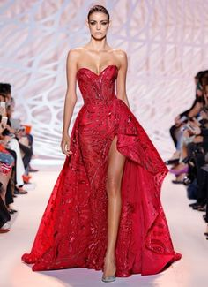 ZUHAIR MURAD - Beaded strapless ball gown in a carmine wave with high slit and asymmetrical ruffle train.