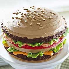 BURGER CAKE! The burgers of this cake are a dark chocolate frosting, the cheese and tomatoes are tinted frosting, the lettuce leaves are made from almond paste, and sunflower seeds stand in for sesame seeds. For for a birthday party or outdoor entertaining.