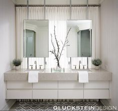 Mounted mirrors in front of the window allow for plenty of light in this stunning principal bath built for two. #glucksteindesign