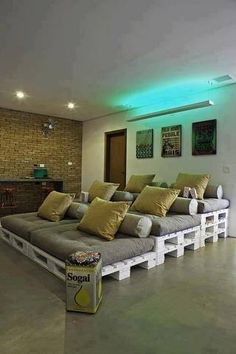 Repurposed wood pallets mutiteared relaxing couch. Green back lighting. Perfect movie room.